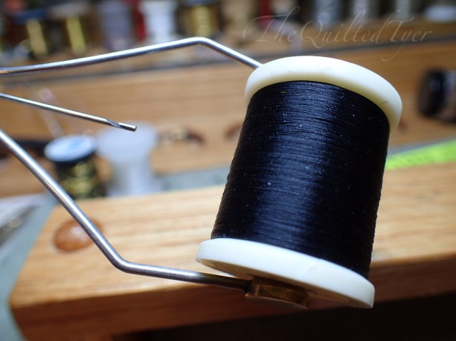 Now Pull a length of thread out of your spool about two inches longer than the length of your bobbin, and hold everything in one hand.