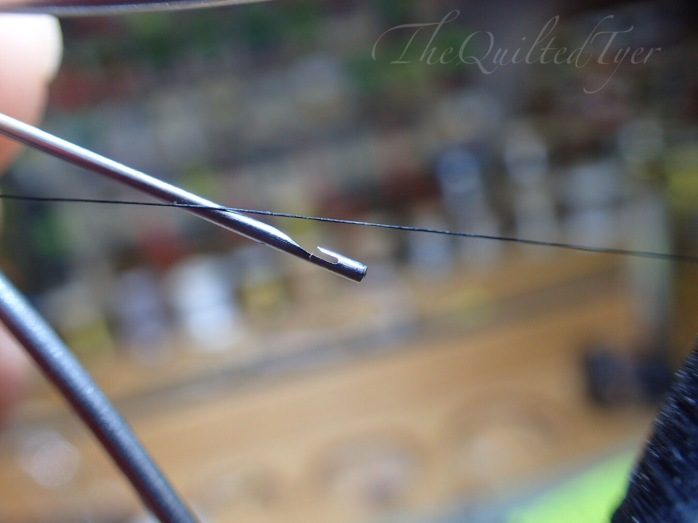 Use one hand to hold bobbin/threader combo and then use the other hand to loop the thread over the hook. If you have a wire bobbin threader you will insert one end of the thread through the wire loop instead.