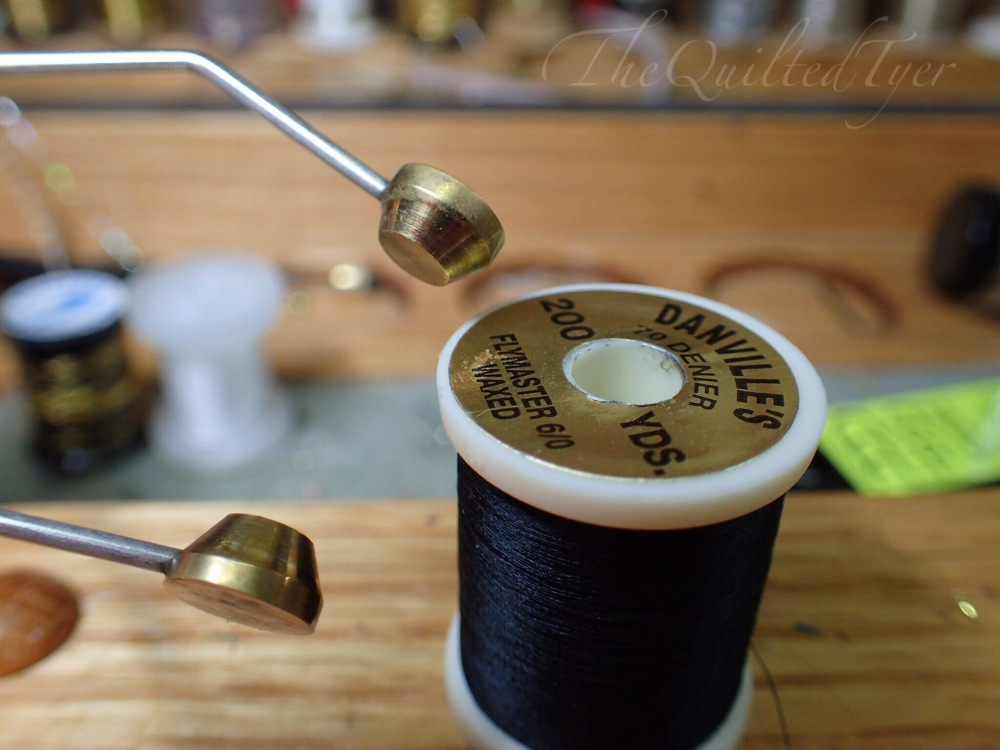 With the holes cleared, take the spool of thread in one hand and the bobbin in the other and position one of the round ends into that spool hole