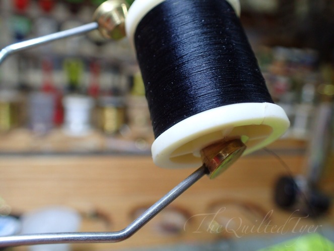 Now with your other hand grab the spool and place one side of it into the bobbin.