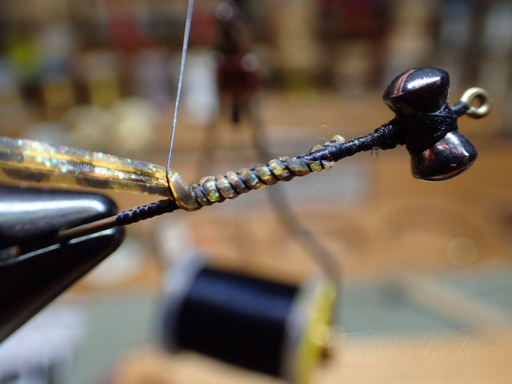 If your material is sliding towards one side of the hook shank, you can fix the problem by pulling the material in the opposite direction that the thread is going.