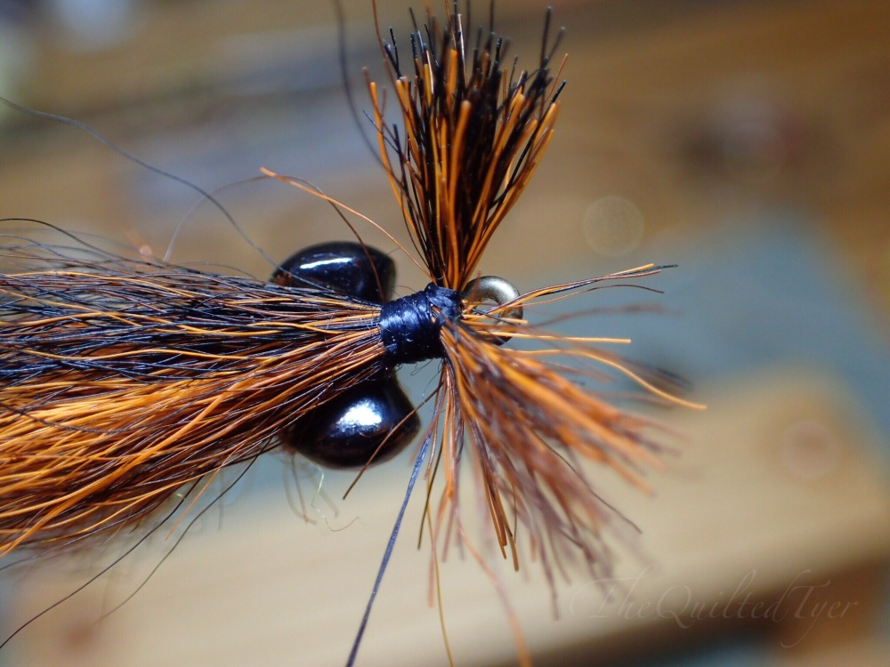 Bring your thread up between the bucktail waste ends, separate it into two