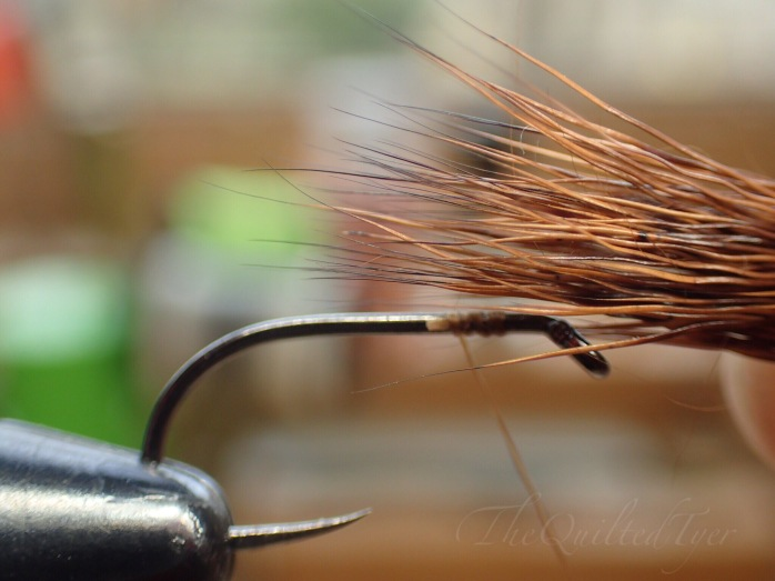 Place your clump of deer hair over the hook shank, and measure it so that the tips land a little past the halfway mark.