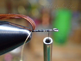 Then continue with a few more wraps, leaving your thread a little ways behind the eye of the shank.